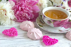 Les pivoines fleurit la tasse rose de la guimauve de coeurs de rotin de thé sur un fond en bois blanc - image courante Photos stock