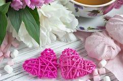 Les pivoines fleurit la tasse rose de la guimauve de coeurs de rotin de thé sur un fond en bois blanc - image courante Images libres de droits