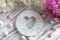 Les pivoines fleurit le rose avec la guimauve en bois blanche de coeur sur un fond en bois blanc - image courante Photographie stock