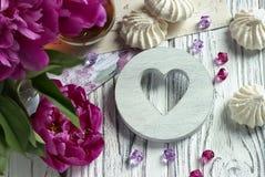 Les pivoines fleurit le verre rose de thé avec la guimauve en bois blanche de coeur sur un fond en bois blanc - image courante Image stock
