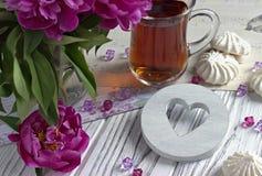 Les pivoines fleurit le verre rose de thé avec la guimauve en bois blanche de coeur sur un fond en bois blanc - image courante Photos stock