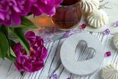 Les pivoines fleurit le verre rose de thé avec la guimauve en bois blanche de coeur sur un fond en bois blanc - image courante Photographie stock