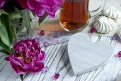 Les pivoines fleurit le verre rose de thé avec la guimauve en bois blanche de coeur sur un fond en bois blanc - image courante Photos libres de droits