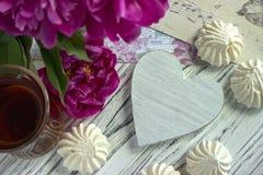 Les pivoines fleurit le verre rose de thé avec la guimauve en bois blanche de coeur sur un fond en bois blanc - image courante Images stock