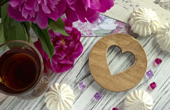 Les pivoines fleurit le verre rose de thé avec la guimauve en bois brune de coeur sur un fond en bois blanc - image courante Images stock