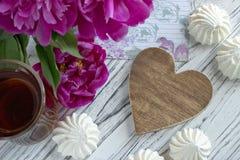 Les pivoines fleurit le verre rose de thé avec la guimauve en bois brune de coeur sur un fond en bois blanc - image courante Image libre de droits