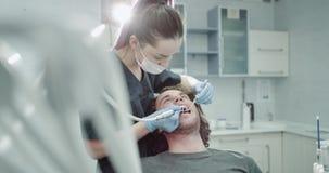 Les plans rapprochés dans des dentis modernes d'une salle de clinique font une procédure d'hygiène buccale au patient de jeune ho banque de vidéos
