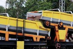 Les plates-formes de train de chemin de fer avec les voitures de gondole qui contiennent une bande de conveyeur avec une bande de images stock