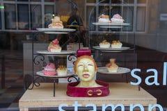 Les plats avec de petits gâteaux dans la fenêtre de la confiserie font des emplettes Images libres de droits