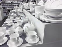 Les plats et les tasses de porcelaine blancs restent sur la table photographie stock