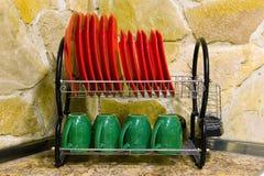 Les plats et les tasses propres se tiennent dans le dessiccateur photographie stock