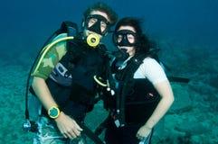 Les plongeurs autonomes posent sous l'eau Photos stock
