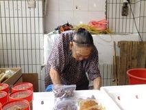 Les plus qu'et 90 vieille dame chinoise an, vente des marchandises sur le marché Photo stock