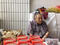 Les plus qu'et 90 vieille dame chinoise an, vente des marchandises sur le marché Images stock