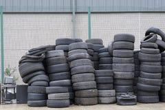Les pneus de voiture ont empilé réutiliser noir en caoutchouc utilisé d'environnement de composé le vieux photos stock