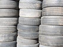 Les pneus utilis?s et vieux ont empil? un sur l'un autre ? c?t? du garage de magasin images stock