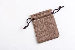 Les poches de bijoux de cadeau de cordon de jute de toile de jute mettent en sac d'isolement au-dessus de la pierre de marbre bla Photo stock