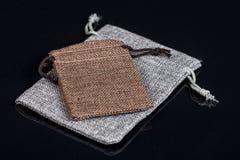 Les poches grises de bijoux de cadeau de cordon de jute de toile de jute mettent en sac au-dessus du fond noir avec des réflexion Photographie stock