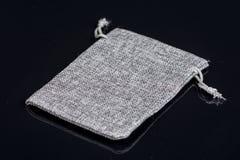 Les poches grises de bijoux de cadeau de cordon de jute de toile de jute mettent en sac au-dessus du fond noir avec des réflexion Image libre de droits