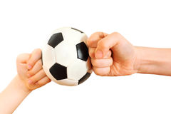Les poings d'enfants se sont reposés dans peu de bille de football Images stock