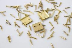 Les pointes d'or et accrochent des peintures à un arrière-plan blanc Photo stock