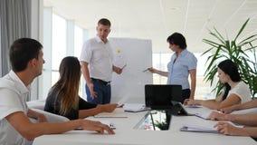 Les points d'homme sur le flipchart offre des idées près des gens d'affaires s'asseyant à la table banque de vidéos