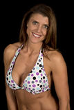 Les points de femme sur le bikini sur le revêtement noir traitent à la légère l'angle Photo stock