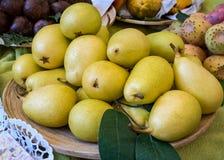 Les poires diminuent la pile d'un plat en bois en marché de vente photo libre de droits