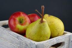 Les poires et la pomme sont ensemble dans la même caisse images stock