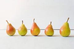 Les poires sur le fond en bois clair, les poires jaunes juteuses mûres se tiennent dans une rangée sur un fond blanc Disposition  Photographie stock libre de droits