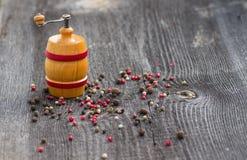 Les pois poivrent et des moulins de poivre sur la table Image libre de droits