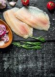 Les poissons ceignent d'un bandeau ? l'oignon coup? en cuvette, ail et romarin photos libres de droits