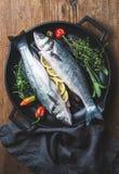 Les poissons crus crus de bar avec des tranches, des herbes et des épices de citron sur griller noir repassent la casserole au-de Images libres de droits