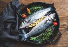 Les poissons crus crus de bar avec des tranches, des herbes et des épices de citron sur griller noir repassent la casserole au-de Photographie stock