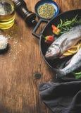 Les poissons crus crus de bar avec du riz, l'huile d'olive, les tranches de citron, les herbes et les épices sur griller noir rep Images stock