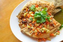 Les poissons cuits à la friteuse avec l'émoi ont fait frire des légumes sur le plat blanc Photographie stock libre de droits
