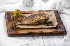 Les poissons grillés épicés ont assaisonné avec le poivre sur un conseil images stock