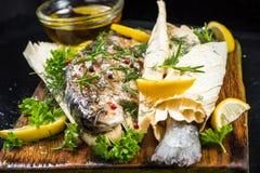 Les poissons ont grillé et ont servi dans la cosse de maïs avec des herbes image libre de droits