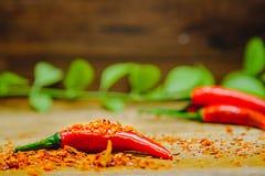 Les poivrons de piment d'un rouge ardent frais sur des piments secs ont coupé avec le fond en bois rustique Photographie stock libre de droits