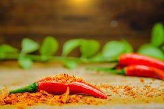 Les poivrons de piment d'un rouge ardent frais sur des piments secs ont coupé avec le fond en bois rustique Concept de nourriture Photographie stock