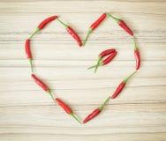Les poivrons de piment ont formé au coeur sur le fond en bois Photographie stock