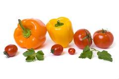 Les poivrons jaunes et oranges avec des tomates sur un fond blanc Légumes multicolores dans une composition sur un fond blanc Photos libres de droits