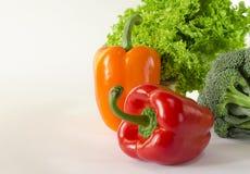Les poivrons rouges et oranges juteux avec une queue verte se trouve à côté du paquet de laitue et le brocoli sont sur un fond bl photographie stock libre de droits