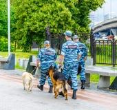 Les policiers et les chiens patrouillent le parc près de l'exposition des accomplissements de l'économie nationale Cynologists ch Photos stock