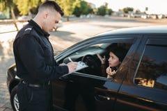Les policiers masculins vérifient le véhicule sur la route photo stock