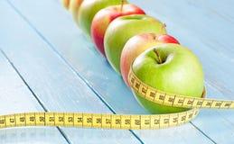 Les pommes avec le ruban métrique sur le fond en bois bleu, perdent le poids Image libre de droits
