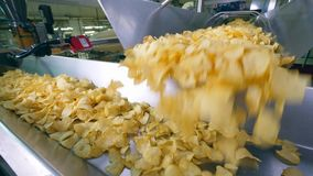 Les pommes chips obtiennent jetées sur le transporteur en métal clips vidéos