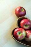 Les pommes dans le plat en bois de forme de coeur sur la table, se ferment  Image stock