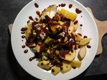 Les pommes de bon goût, oranges, kiwi ont complété avec du chocolat du plat blanc Images stock