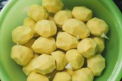 les pommes de terre épluchées se situent dans une cuvette verte avec de l'eau cuisson des pommes de terre faites maison photos stock